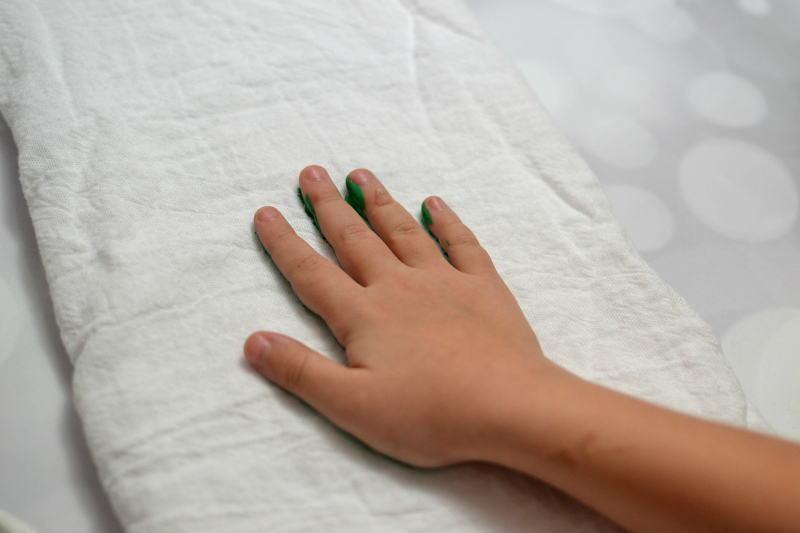 The first step in making your Christmas Tree Handprint Towel is, of course, to place your child's handprint in green paint.