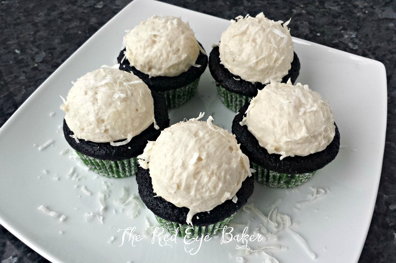 Dark Chocolate Coconut Cupcakes topped with a perfect mound of coconut frosting that's filled with flaked coconut. A coconut lovers dream!