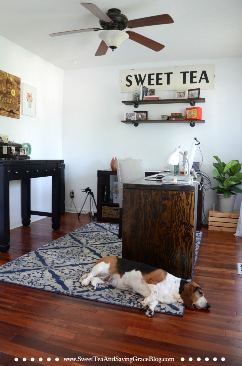 I love the look of rustic, industrial furniture, but for my home office, I had to add a few feminine touches, too. The clean, white walls, industrial shelving, custom-built desk, one-of-a-kind handmade sign, antique pieces make this rustic home office cozy and professional.